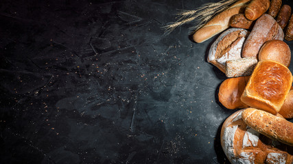 Zelfklevend Fotobehang Bakkerij Assortment of fresh baked bread on dark background. White and rye bread, buns with copy place