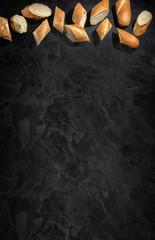 Papiers peints Beton Sliced fresh crunchy baguette on dark background. Top view with copy place