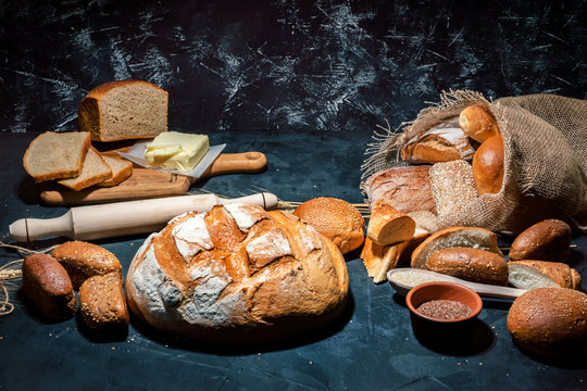 Different kinds of bread and bread rolls on dark background. Assortment of fresh baked bread, sweet pastries, baked goods, white and rye bread