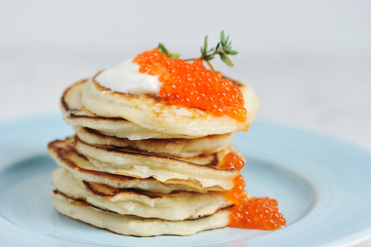 Pancakes with red caviar and sour cream on a plate. Light background. Close-up. Macro shooting. The concept of a festive feast.