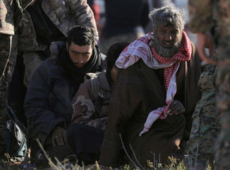 Men are detained by the Syrian Democratic Forces (SDF) after coming out from last Islamic State pocket, near the village of Baghouz, Deir Al Zor province