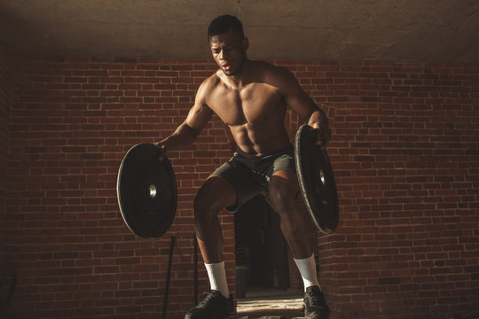 Athletic dark-skinned fitness coach working out with crossfit jumps on giant tire with weighting, therefore training the heart, legs, abdominal muscles and overall endurance.