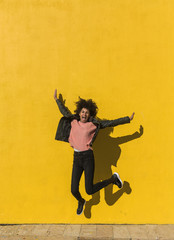 Black woman with afro hair jumping for joy in the street with a yellow wall in the background