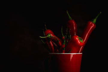 Fresh red and spicy chilli peppers on dark background.