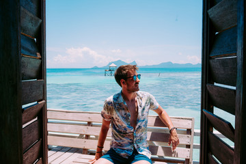 Young guy in sunglasses sitting on seat near blue sea and looking away in Jamaica
