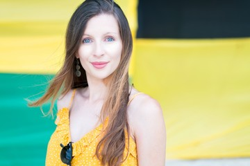 Charming beautiful young woman with sunglasses on yellow blouse looking at camera on blurred background in Jamaica