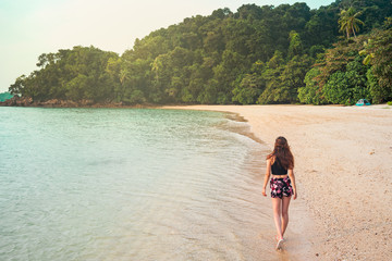 Back view of slim lady walking on sand beach near sea and green tropical forest in Jamaica