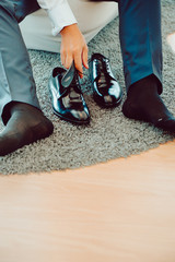 Crop male in trousers sitting and wearing black elegant boots on carpet
