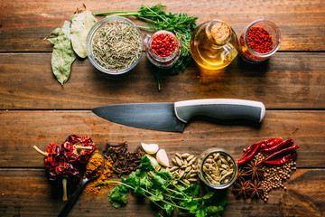 From above various spices and bottle of oil placed on timber tabletop near sharp knife