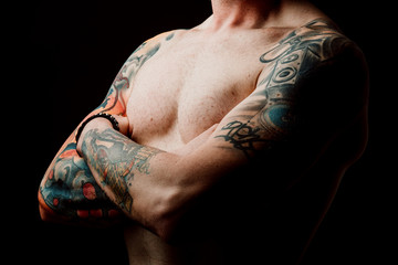 Side view of crop shirtless hipster with crossed hands and tattoos on hands on black background