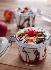 Close-up of peach parfait with yogurt, granola and chocolate topping in a jar