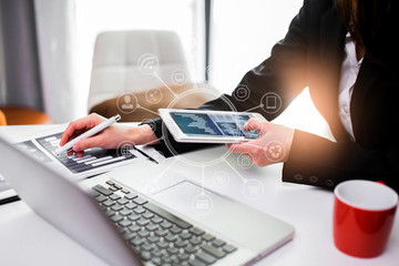businesswoman working on smart phone with laptop in office