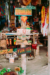 Wood pole with tablets with different words near small souvenir shop in Jamaica