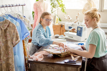 Couple of young beautiful business women starting their own small tailoring business, seamstress and fashion designer make sketches and pick up fabrics while preparing for an exhibition