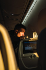 Thoughtful man looking out plane window