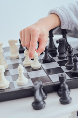 Crop hand of child holding figure on chess board on grey background