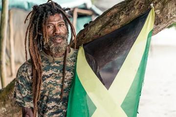 African American bearded male with dreadlocks holding Jamaica flag near tree