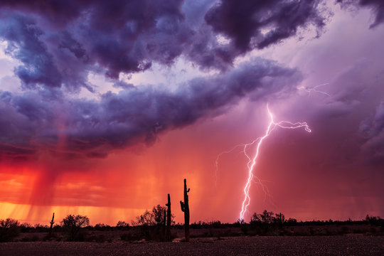Lightning bolt strikes from a storm at sunset.