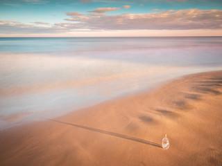 Bottle in sand near sea