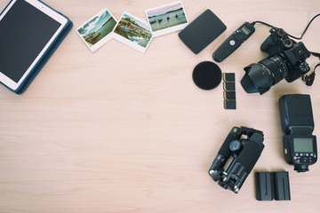 From above professional camera near equipments, tablet and vintage shots on wood background