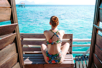 Back view of lady in swimsuit and sunglasses sitting on seat near blue sea in Jamaica