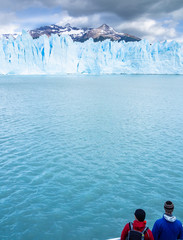 Back view of two tourists admiring calm cold sea and spectacular ice cliff on cloudy day in Argentina