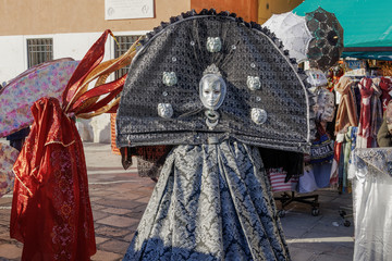 Venice, Italy Carnival mask and costume pose in Saint Mark square. Masked person in traditional costume poses at a Venetian square during the Venice 2019 Carnival.