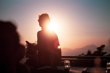 A teenager enjoys the sunset in a restaurant with a panoramic view and looks into the distance. Some objective reflections and warm colours.