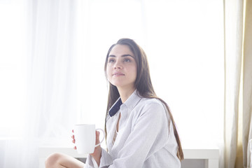 Young beautiful happy brunette woman in black silk dressing gown lying in bed, drinking morning coffee, white cup. Womens day holiday