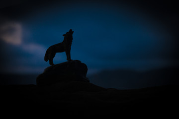 Silhouette of howling wolf against dark toned foggy background. Halloween horror concept.