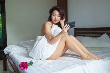 Portrait of Asia girl on the white bed in the bed room