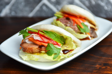 Fresh delicious pork steamed buns with BBQ sauce, coriander, mint, salad leaf and vegetables carrots, capsicum