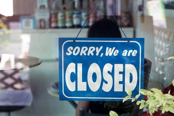 Sorry we are closed sign hanging on the door of cafe.