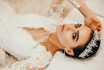 beautiful sensual bride with dark hair in luxurious wedding dress and accessories