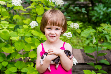 Portrait of smiling 3-years old girl with 4-days-old Estonian Hound puppy. Summertime in countryside.