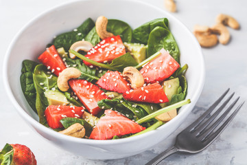 Summer strawberry avocado salad with cashews in a white bowl.