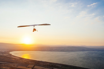 Hang-glider  flight in sky in sunset time over the Kineret, Mevo Hama, Israel