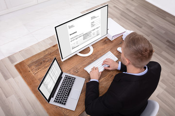 Smiling Businessman Checking Invoice On Computer
