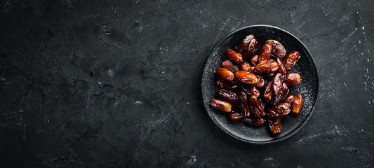 Dry date in a bowl on a black background. Dried fruit Top view. Free space for your text.