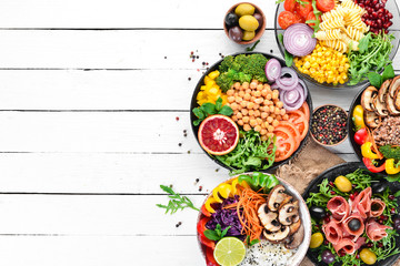 Fotomurales - Buddha bowl on a white wooden background. Assortment of healthy food. Top view. Free space for your text.