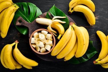 Bananas on a black wooden surface. Tropical Fruits. Top view. Free copy space.