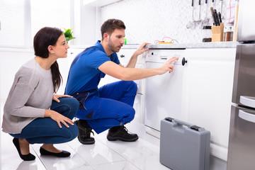 Serviceman Pressing Button Of Dishwasher In Kitchen
