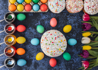 Easter.Colorful eggs,spring tulips,cakes on blue background.Holiday set.Happy religious day,traditional for people. Top view.Copy space.Concept
