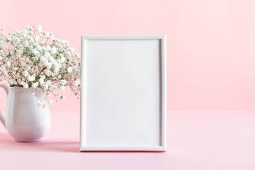 Home interior floral decor. White gypsophila flowers, photo frame. Elegant floral soft pink composition. Beautiful flowers in vase on pastel pink wall background