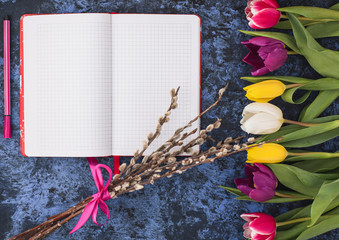 Easter.Notebook for writing,spring tulips,willow tree on blue background.t.Happy religious day,traditional for people. Top view.Copy space.Concept
