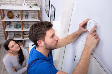 Obraz Repairman Installing Smoke Detector On Wall - fototapety do salonu