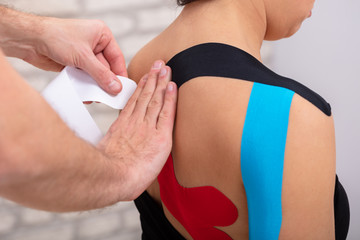 Man Hand's Applying Red Physio Tape On Woman's Back
