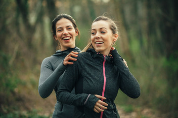 Two young beautiful woman exercise in the forest