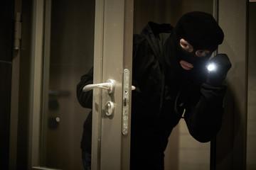 Burglar thief in mask. break-in of an apartment. - fototapety na wymiar