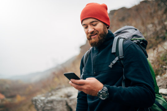 Young bearded man smiling and sending messages for his family from his cellphone, during hiking in mountains. Traveler bearded man in red hat using mobile phone application. Travel and lifestyle